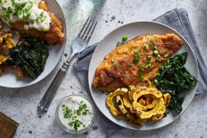 panfried catfish dinner with squash and spinach in flat lay comp
