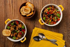 Traditional Italian caponata, served with croutons in a yellow,